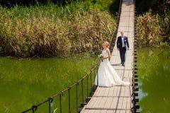 Νεόνυμφος που πηγαίνει στη νύφη κατά μήκος της γέφυρας Στοκ Φωτογραφίες