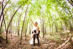 Νεόνυμφος που τρέχει μακριά με τη νύφη στην πλάτη του στο πάρκο στοκ φωτογραφία