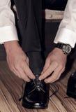 Νεόνυμφος που φορά τα παπούτσια στη ημέρα γάμου, που δένει τις δαντέλλες Στοκ Εικόνες