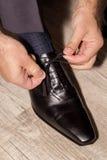 Νεόνυμφος που φορά τα παπούτσια στη ημέρα γάμου, που δένει τις δαντέλλες Στοκ φωτογραφίες με δικαίωμα ελεύθερης χρήσης