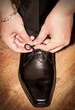 Νεόνυμφος που φορά τα παπούτσια στη ημέρα γάμου, που δένει τις δαντέλλες Στοκ Φωτογραφίες