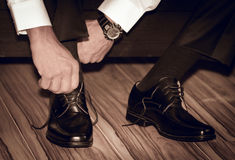 Νεόνυμφος που φορά τα παπούτσια στη ημέρα γάμου, που δένει τις δαντέλλες Στοκ εικόνες με δικαίωμα ελεύθερης χρήσης