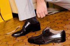 Νεόνυμφος που φορά τα παπούτσια στη ημέρα γάμου, που δένει τις δαντέλλες Στοκ εικόνα με δικαίωμα ελεύθερης χρήσης