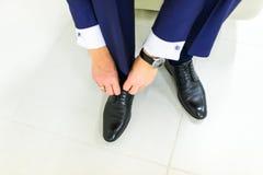 Νεόνυμφος που φορά τα παπούτσια στη ημέρα γάμου, τη σύνδεση των δαντελλών και να προετοιμαστεί Επιχειρησιακό άτομο που ντύνει επά Στοκ Εικόνες
