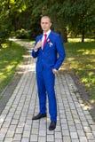 Νεόνυμφος σε ένα μπλε κοστούμι που στέκεται στην αλέα Στοκ Εικόνα