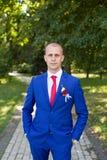 Νεόνυμφος σε ένα μπλε κοστούμι που στέκεται στην αλέα Στοκ εικόνα με δικαίωμα ελεύθερης χρήσης