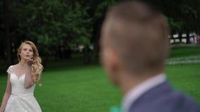 Νεόνυμφος φιλιών νυφών στο πάρκο απόθεμα βίντεο
