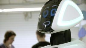 Νεώτερη ρομποτική τεχνολογία το ρομπότ χαμογελά και εξετάζει τη κάμερα το φιλικό ρομπότ humanoid παρουσιάζει ενδιαφέρον για τον κ απόθεμα βίντεο