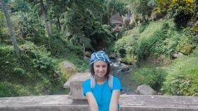 Νησί του Μπαλί Μια εξόρμηση στο νησί Το κορίτσι στο μπλε πουκάμισο περπατά στη γέφυρα πετρών Το brunette με τη βοήθεια του α απόθεμα βίντεο