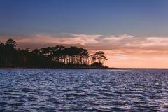 Νησί Assateague στο ηλιοβασίλεμα πέρα από το νερό Στοκ Εικόνα