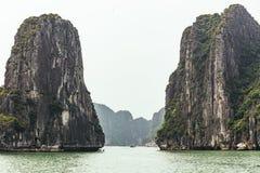 Νησιά ασβεστόλιθων στο αριστερό και τη δεξιά πλευρά πέρα από το σμαραγδένιο νερό με το φωτεινό ουρανό το καλοκαίρι σε Quang Ninh, στοκ εικόνες