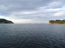 Νησιά μακρυά μεταξύ δύο ακρωτηρίων στην ήρεμη θάλασσα κάτω από τα σύννεφα στο ηλιοβασίλεμα Στοκ φωτογραφία με δικαίωμα ελεύθερης χρήσης