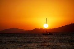 Νησιά, μπλε θάλασσα και μπλε βάρκες γύρου ιστιοπλοϊκά, ηλιοβασίλεμα Στοκ Εικόνα