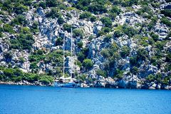 Νησιά, μπλε θάλασσα και μπλε βάρκες γύρου ιστιοπλοϊκά Στοκ εικόνα με δικαίωμα ελεύθερης χρήσης
