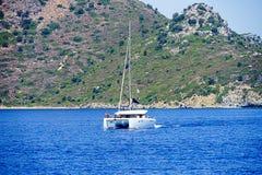 Νησιά, μπλε θάλασσα και μπλε βάρκες γύρου ιστιοπλοϊκά Στοκ Εικόνα