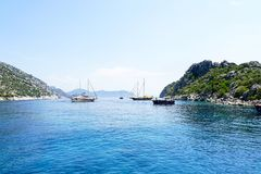 Νησιά, μπλε θάλασσα και μπλε βάρκες γύρου ιστιοπλοϊκά Στοκ Φωτογραφία
