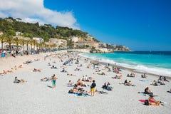 ΝΙΚΑΙΑ, ΓΑΛΛΙΑ - 22 Απριλίου 2017: Άνθρωποι που κάνουν ηλιοθεραπεία και που χαλαρώνουν στην παραλία στη Νίκαια, Γαλλία Στοκ Εικόνες