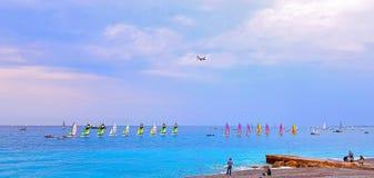 ΝΙΚΑΙΑ, ΓΑΛΛΙΑ - ΤΟ ΜΆΙΟ ΤΟΥ 2018: Παραλία στο ηλιοβασίλεμα, ζωηρόχρωμα sailboats στη θάλασσα, αεροπλάνο που πετά πέρα από τη θάλ στοκ εικόνα
