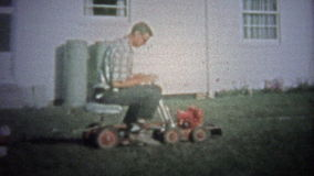 ΝΙΟΥ ΧΆΒΕΝ, CONN ΗΠΑ - 1957: Μπαμπάς στα νέα οδηγώντας ρυμουλκώντας παιδιά θεριστών χορτοταπήτων στην πλάτη απόθεμα βίντεο