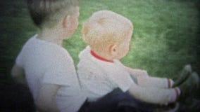 ΝΙΟΥ ΧΆΒΕΝ, CONN ΗΠΑ - 1957: Mom στα νέα οδηγώντας ρυμουλκώντας παιδιά θεριστών χορτοταπήτων στην πλάτη απόθεμα βίντεο