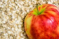 Νιφάδες βρωμών της Apple στο υπόβαθρο (εστίαση στο μήλο) Στοκ Φωτογραφίες