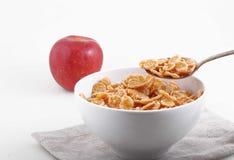 Νιφάδες καλαμποκιού και ρυζιού στο άσπρο κύπελλο και την κόκκινη Apple Στοκ εικόνες με δικαίωμα ελεύθερης χρήσης