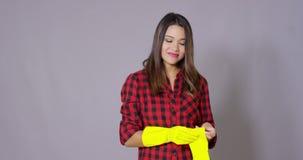 νοικοκυρά γαντιών που βάζει τις λαστιχένιες νεολαίες απόθεμα βίντεο