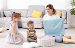 Νοικοκυρά με τα παιδιά που διπλώνουν τις πρόσφατα πλυμένες πετσέτες Στοκ φωτογραφία με δικαίωμα ελεύθερης χρήσης