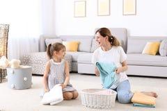 Νοικοκυρά με την κόρη που διπλώνει τις πρόσφατα πλυμένες πετσέτες στοκ φωτογραφία