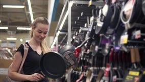 Νοικοκυρά που αγοράζει τα νέα τηγάνια στο κατάστημα απόθεμα βίντεο
