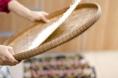 Νοικοκυρά που επιλέγει το ρύζι με τη χρησιμοποίηση της καλαθοπλεκτικής μπαμπού για χωριστό μεταξύ του ρυζιού και του φλοιού ρυζιο Στοκ Εικόνες