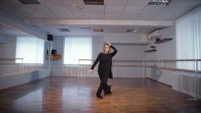Νοικοκυρά που κάνει το αγαπημένο χόμπι της Η ενήλικη γυναίκα είναι χορεύοντας ένας νέος χορός σε ένα στούντιο χορού Μετακίνηση τω φιλμ μικρού μήκους