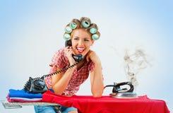 Νοικοκυρά που μιλά στο τηλέφωνο σιδερώνοντας Στοκ εικόνες με δικαίωμα ελεύθερης χρήσης