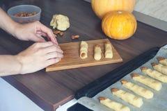 Νοικοκυρά που φορμάρει τα μπισκότα αποκριών με το χέρι της από τη ζύμη στην κουζίνα Παραδοσιακές διακοπές φθινοπώρου Στοκ Φωτογραφία