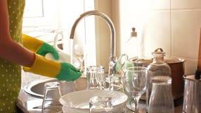 Νοικοκυρά στα λαστιχένια γάντια που πλένουν τα πιάτα απόθεμα βίντεο