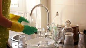 Νοικοκυρά στα λαστιχένια γάντια που πλένουν τα πιάτα φιλμ μικρού μήκους