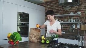 Νοικοκυρά στην κουζίνα με μια τσάντα των φρούτων απόθεμα βίντεο