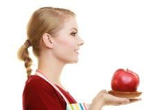 Νοικοκυρά στην ποδιά κουζινών που προσφέρει στο μήλο τα υγιή φρούτα Στοκ Εικόνες