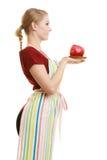 Νοικοκυρά στην ποδιά κουζινών που προσφέρει στο μήλο τα υγιή φρούτα Στοκ Φωτογραφία