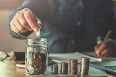 νομίσματα εκμετάλλευσης χεριών επιχειρησιακών γυναικών που υποβάλλουν το γυαλί έννοια finan στοκ εικόνες