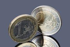 Νομίσματα ενός και δύο ευρώ σε ένα γκρίζο υπόβαθρο Στοκ εικόνα με δικαίωμα ελεύθερης χρήσης