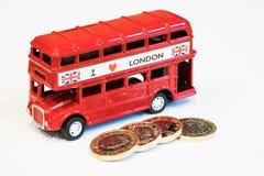 Νομίσματα λεωφορείων του Λονδίνου και 1 λίβρας Στοκ Φωτογραφίες