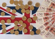 Νομίσματα λιβρών και χαρτονόμισμα, Ηνωμένο Βασίλειο πέρα από τη σημαία Στοκ Φωτογραφίες