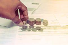 Νομίσματα και λογαριασμός με την αποταμίευση χεριών για τη ζωή Στοκ Φωτογραφίες