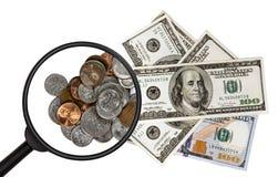 Νομίσματα και τραπεζογραμμάτια κάτω από μια ενίσχυση - γυαλί που απομονώνεται στο λευκό Στοκ φωτογραφία με δικαίωμα ελεύθερης χρήσης