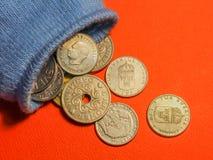 Νομίσματα που ανατρέπουν έξω από μια μπλε κάλτσα στοκ φωτογραφίες