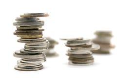 Νομίσματα που συσσωρεύονται στο άσπρο υπόβαθρο Στοκ Φωτογραφίες