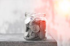 Νομίσματα σε ένα βάζο γυαλιού ενάντια, τα νομίσματα αποταμίευσης - επένδυση και έννοια χρημάτων αποταμίευσης έννοιας ενδιαφέροντο Στοκ Φωτογραφία