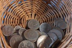 Νομίσματα σε ένα καλάθι Στοκ Εικόνες