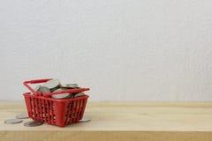 Νομίσματα σε ένα κόκκινο καλαθιών για την έννοια χρημάτων Στοκ φωτογραφίες με δικαίωμα ελεύθερης χρήσης